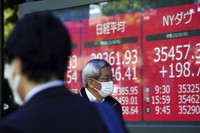 A man wearing a protective mask looks at an electronic stock board showing Japan's Nikkei 225, center, and New York Dow indexes at a securities firm on Oct. 20, 2021, in Tokyo. (AP Photo/Eugene Hoshiko)