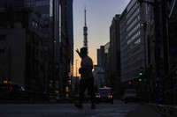 A man hails a taxi in Roppingi neighborhood, an entertainment district, in Tokyo on Oct. 20, 2021, as Tokyo Tower is silhouetted against the sunrise colored sky in the background.(AP Photo/Kiichiro Sato)