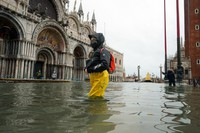In this Dec. 8, 2020 file photo, people wade their way through water in flooded St. Mark's Square following a high tide, in Venice, Italy. (Anteo Marinoni/LaPresse via AP)