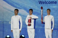 Volunteers hold the Olympic torch and the frame on stage during a welcome ceremony for the Frame of Olympic Winter Games Beijing 2022, held at the Olympic Tower in Beijing, on Oct. 20, 2021. (AP Photo/Andy Wong)