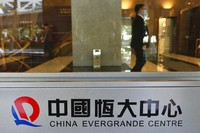 In this Oct. 4, 2021, file photo, a security guard stands at the headquarters of China Evergrande Group in Hong Kong. (AP Photo/Vincent Yu)
