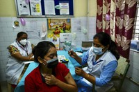 A health worker inoculates a woman at a government hospital in New Delhi, India, on Oct. 21, 2021. (AP Photo/Manish Swarup)