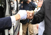 衆議院議員選挙の出陣式で、新型コロナウイルス感染症予防のため支援者とグータッチをする候補者(左)=京都市下京区で2021年10月19日、山崎一輝撮影