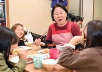Yasuko Kawabe, representative director of Nishinari Child Care Center, is seen eating dinner with kids at the children's cafeteria operated by the nonprofit group in the city of Osaka's Nishinari Ward, on Oct. 18, 2021. (Mainichi/Daiki Takikawa)