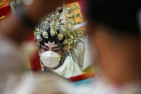 A Chinese opera performer wearing a face mask to help curb the spread of the coronavirus prepares for the stage in Bangkok, Thailand, on Oct. 6, 2021. (AP Photo/Sakchai Lalit)