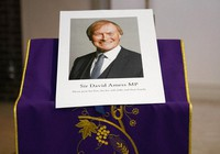 In this Oct. 15, 2021 file photo, an image of murdered British Conservative lawmaker David Amess is displayed near the altar in St Peters Catholic Church before a vigil in Leigh-on-Sea, Essex, England. (AP Photo/Alberto Pezzali)