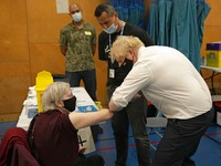 British Prime Minister Boris Johnson greets 88-year-old Nitza Sarner as she waits to receive a pfizer booster vaccination as he visits a COVID-19 vaccination centre at Little Venice Sports Centre, in London, on Oct. 22, 2021. (AP Photo/Matt Dunham, Pool)