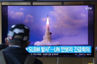 """A man watches a TV screen showing an image of North Korea's ballistic missile launched from a submarine during a news program at Seoul Railway Station in Seoul, South Korea, on Wednesday, Oct. 20, 2021. The Korean characters read: """"North Korea launched a Submarine-Launched Ballistic Missile ... U.N. security council emergency meeting."""" (AP Photo/Ahn Young-joon)"""