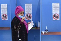 A woman walks to cast her ballot at a polling station during the presidential election in Tashkent, Uzbekistan, Sunday, Oct. 24, 2021. (AP Photo)