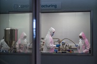 Scientists re-enact the calibration procedure of equipment at an Afrigen Biologics and Vaccines facility in Cape Town, South Africa, Tuesday Oct. 19, 2021. (AP Photo/Jerome Delay)