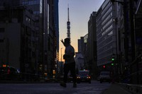 A man hails a taxi in Roppingi neighborhood, an entertainment district, in Tokyo Wednesday, Oct. 20, 2021, as Tokyo Tower is silhouetted against the sunrise colored sky in the background. (AP Photo/Kiichiro Sato)