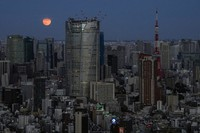 The full moon rises above the Tokyo skyline, Oct. 20, 2021. (AP Photo/Kiichiro Sato)