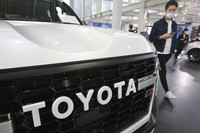 A man walks by the logo on a Toyota car at a showroom in Tokyo on Oct. 18, 2021. (AP Photo/Koji Sasahara)
