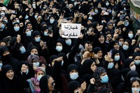 """In this Oct. 15, 2021, mourners chant slogans as they hold a placard with Arabic that reads """"Our choice is resistance"""" during the funeral of three Hezbollah supporters who were killed during clashes, in the southern Beirut suburb of Dahiyeh, Lebanon. (AP Photo/Bilal Hussein)"""