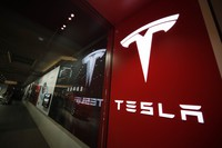 This Feb. 9, 2019 file photo shows a sign bearing the company logo outside a Tesla store in Cherry Creek Mall in Denver. (AP Photo/David Zalubowski)