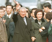 In this Dec. 22, 1997, file photo former South Korean President Roh Tae-woo, with his wife Kim Ok-sook standing beside him, waves to his supporters and neighbors upon arrival at his home after he was released from the Seoul prison in a special amnesty. (Yonhap via AP)