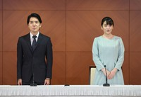 Kei, left, and Mako Komuro are seen at the end of a news conference in Tokyo's Chiyoda Ward after their marriage on Oct. 26, 2021. (Pool photo)
