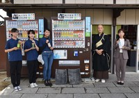 Those involved in the project pose for a photo in front of the vending machines with donation buttons at a rest area near Kofukuji temple's Nanendo southern round hall in the city of Nara on Oct. 12, 2021. (Mainichi/Yuhi Yoshikawa)