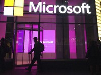 In this Nov. 10, 2016, file photo, people walk past a Microsoft office in New York. (AP Photo/Swayne B. Hall)