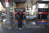 A worker leans against a gasoline pump that has been turned off, at a gas station in Tehran, Iran, on Oct. 26, 2021. (AP Photo/Vahid Salemi)
