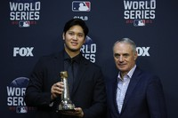 Shohei Ohtani holds the Commissioner's Historic Achievement Award from Rob Manfred before Game 1 in baseball's World Series between the Houston Astros and the Atlanta Braves on Oct. 26, 2021, in Houston. (AP Photo/Ashley Landis)