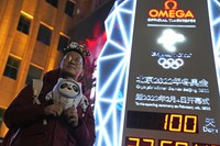 A person poses for photos with a countdown clock as it hits 100 days to the opening of the 2022 Beijing Winter Olympics, in Beijing, on Oct. 26, 2021. (AP Photo/Ng Han Guan)