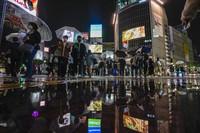 People wearing masks walk around the famed Shibuya scramble crossing in Tokyo, on Oct. 25, 2021, in Tokyo. (AP Photo/Kiichiro Sato)