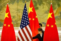 In this Feb. 14, 2019 file photo, Chinese staffers adjust U.S. and Chinese flags before the opening session of trade negotiations between U.S. and Chinese trade representatives at the Diaoyutai State Guesthouse in Beijing. (AP Photo/Mark Schiefelbein)