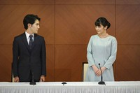 Japan's former Princess Mako, right, the elder daughter of Crown Prince Akishino and Crown Princess Kiko, and her husband Kei Komuro, look at each other during a press conference to announce their marriage at a hotel in Tokyo, Japan on Oct. 26, 2021. (Nicolas Datiche/Pool Photo via AP)